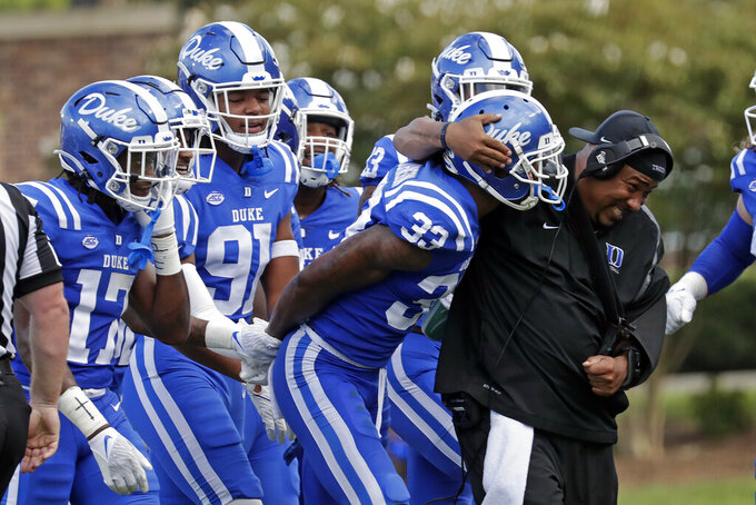 Duke cornerback Leonard Johnson (33) is congratulated by teammates and coaches after he intercepted a pass against Northwestern during the first half of an NCAA college football game in Durham, N.C., Saturday, Sept. 18, 2021. (AP Photo/Chris Seward)
