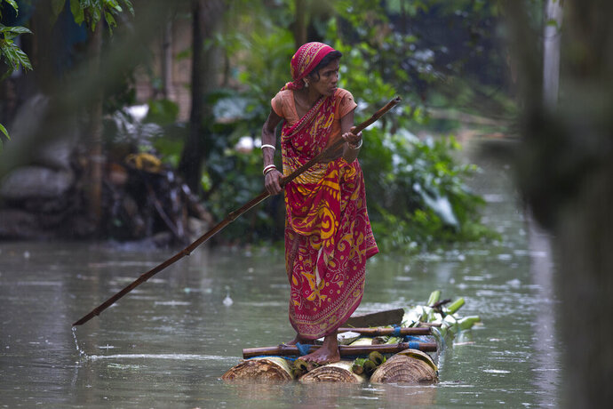 An Indian woman rows a makeshift banana raft through flood waters in Burgaon, east of Gauhati, Assam, India, Monday, July 15, 2019. After causing flooding and landslides in Nepal, three rivers are overflowing in northeastern India and submerging parts of the region, affecting the lives of more than 2 million, officials said Monday. (AP Photo/Anupam Nath)