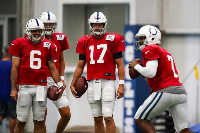 Indianapolis Colts quarterback Philip Rivers (17) watches as quarterback Jacoby Brissett (7) throws during practice at the NFL team's football training camp in Indianapolis, Tuesday, Aug. 18, 2020. (AP Photo/Michael Conroy)