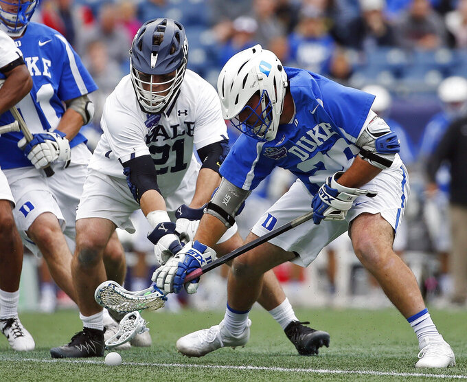 FILE - In this May 28, 2018, file photo, Yale's Conor Mackie (21) battles Duke's Brian Smyth, right, for the ball during the first half in the championship game of the NCAA college Division I lacrosse tournament in Foxborough, Mass. The men's lacrosse tournament which gets underway in earnest this weekend when Yale hosts Big East champion Georgetown in a first-round game on Saturday (AP Photo/Michael Dwyer, File)