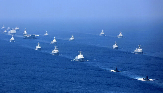 FILE - In this April 12, 2018, file photo released by China's Xinhua News Agency, the Liaoning aircraft carrier is accompanied by navy frigates and submarines conducting an exercises in the South China Sea. Despite the coronavirus outbreak, China is keeping up with military exercises around Taiwan at the northern edge of the South China Sea. (Li Gang/Xinhua via AP, File)