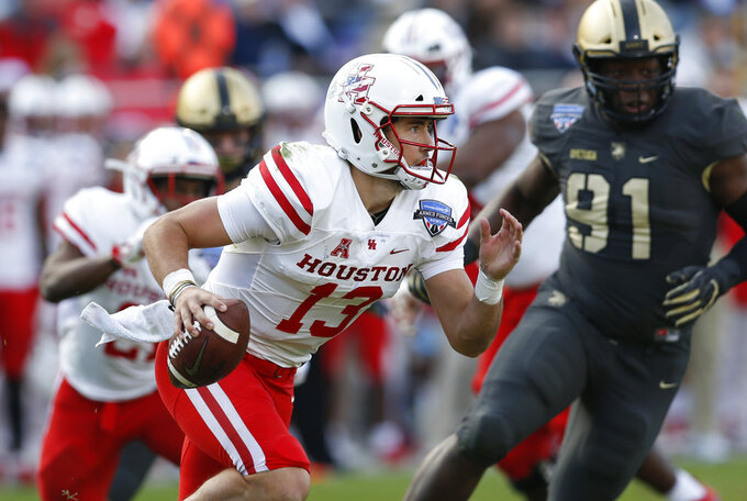 Houston quarterback Clayton Tune (13) runs out of the pocket pursued by Army defensive lineman Wunmi Oyetuga (91) during the first half of Armed Forces Bowl NCAA college football game Saturday, Dec. 22, 2018, in Fort Worth, Texas. (AP Photo/Jim Cowsert)