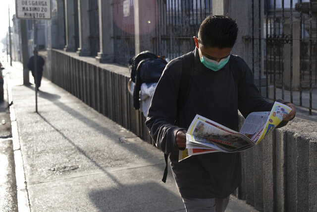A man wearing a protective mask reads newspaper in Guatemala City, Tuesday, March 17, 2020. Guatemalan President Alejandro Giammattei effectively closed off Guatemala late Monday to all non-Guatemalans or permanent residents and ordered a suspension of all non-essential activities. For most people, the new coronavirus causes only mild or moderate symptoms. For some it can cause more severe illness. (AP Photo/Moises Castillo)