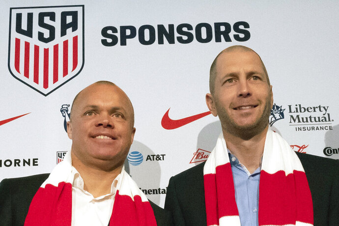 FILE - In this Dec. 4, 2018, file photo, Earnie Stewart, general manager of the U.S. men's national soccer team, and head coach Gregg Berhalter pose at a news conference in New York. The sporting director of the U.S. Soccer Federation says Gregg Berhalter's job is safe as men's national team coach despite some disappointing results.
