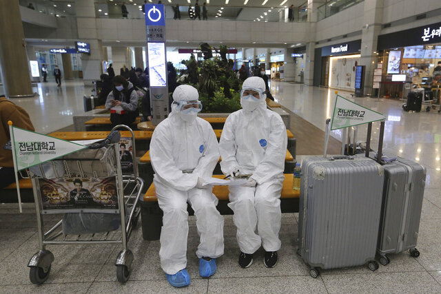 Chonnam National University staff wearing protective attire are on standby for special transportation for Chinese students studying at their university, at Incheon International Airport in Incheon, South Korea, Tuesday, Feb. 25, 2020. Chinese students of the university are to arrive from China after their holiday. China and South Korea on Tuesday reported more cases of a new viral illness that has been concentrated in North Asia but is causing global worry as clusters grow in the Middle East and Europe. (AP Photo/Ahn Young-joon)