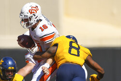 West Virginia defensive end VanDarius Cowan (8) tackles Oklahoma State  cornerback Jordan Reagan (26) during an NCAA college football game Saturday, Sept. 26, 2020, in Stillwater, Okla. (AP Photo/Brody Schmidt)