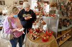 Ronda Harrington, left, shops for gifts with Barbara Sides, right, in Mississippi Mud in Kimmswick, Mo., on Sunday, Oct. 18, 2020. Businesses are receiving large support from the community after being hit by COVID-19 as well as the cancellation of the annual Apple Butter Festival.   (Christine Tannous /St. Louis Post-Dispatch via AP)
