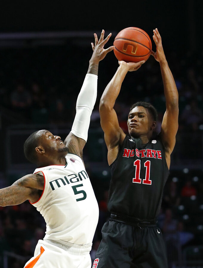 North Carolina State guard Markell Johnson (11) takes a shot against Miami guard Zach Johnson (5) during the second half of an NCAA college basketball game, Thursday, Jan. 3, 2019, in Coral Gables, Fla. North Carolina State defeated Miami 87-82. (AP Photo/Wilfredo Lee)