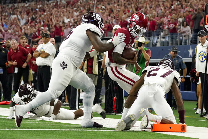 Texas A&M defensive lineman Adarious Jones, left, and defensive back Antonio Johnson (27) stop Arkansas quarterback Malik Hornsby (4) from reaching the end zone on a carry in the second half of an NCAA college football game in Arlington, Texas, Saturday, Sept. 25, 2021. (AP Photo/Tony Gutierrez)