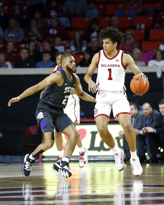 Oklahoma's Jalen Hill (1) goes against TCU's Edric Dennis Jr. (2) during the first half of an NCAA college basketball game in Norman, Okla., Saturday, Jan. 18, 2020. (AP Photo/Garett Fisbeck)