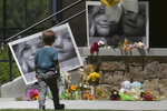 FILE - In this June 11, 2020, file photo, a boy looks at a memorial for Tylee Ryan, 17, and Joshua