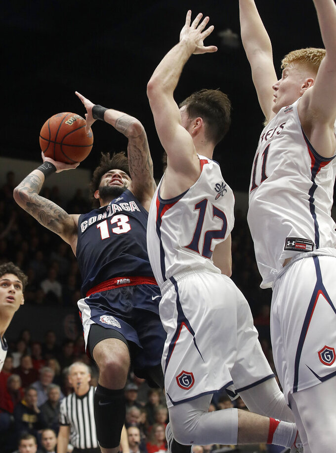 Gonzaga guard Josh Perkins (13) shoots against Saint Mary's guard Tommy Kuhse (12) and forward Matthias Tass (11) during the first half of an NCAA college basketball game in Moraga, Calif., Saturday, March 2, 2019. (AP Photo/Jeff Chiu)