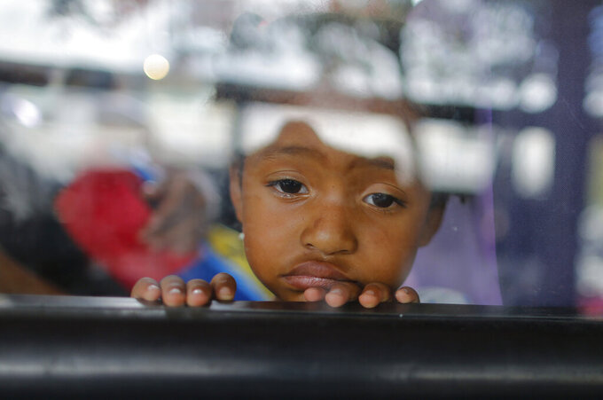 A girl looks out of a bus window in Caracas, Venezuela, Wednesday, Feb. 19, 2020. The debate over fresh U.S. sanctions aimed at forcing out Venezuela's Nicolás Maduro played out Wednesday across the crisis-stricken South American nation. Families have been split up with at least 4.5 million Venezuelans fleeing crumbling public services. (AP Photo/Ariana Cubillos)