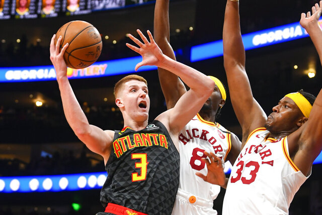 Atlanta Hawks guard Kevin Huerter (3) shoots as Indiana Pacers forward Justin Holiday (8) and center Myles Turner (33) defend during the first half of an NBA basketball game Saturday, Jan. 4, 2020, in Atlanta. (AP Photo/John Amis)