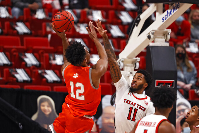 Sam Houston State's Tristan Ikpe (12) shoots the ball over Texas Tech's Kyler Edwards (11) during the first half of an NCAA college basketball game Friday, Nov. 27, 2020, in Lubbock, Texas. (AP Photo/Brad Tollefson)