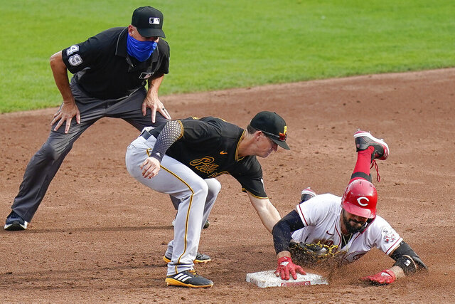 Cincinnati Reds' Nicholas Castellanos, right, slides safely into second base while avoiding the tag of Pittsburgh Pirates shortstop Kevin Newman, center, during the third inning of a baseball game at Great American Ballpark in Cincinnati, Thursday, Aug. 13, 2020. (AP Photo/Bryan Woolston)