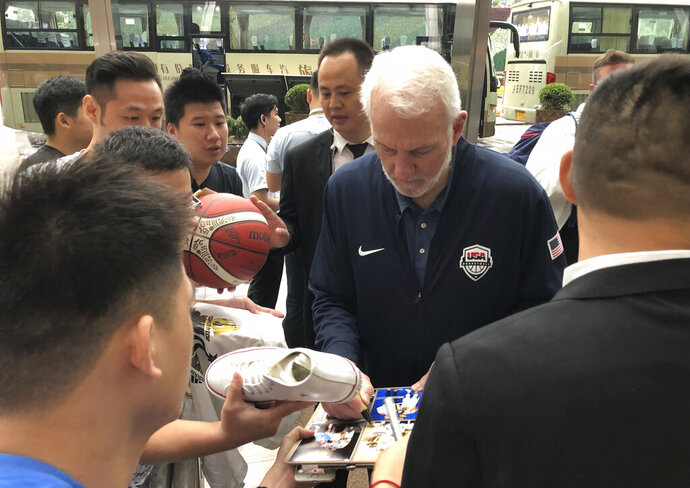 U.S. men's basketball coach Gregg Popovich signs autographs for fans Thursday, Aug. 29, 2019, at the team hotel in Shanghai upon arrival for the World Cup. The team will play three first-round games starting Sunday. (AP Photo/Tim Reynolds)