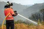 A forest firefighter works in a wildfire in Estepona, Spain, Thursday, Sept. 9, 2021. Nearly 800 people have been evacuated from their homes and road traffic has been disrupted as firefighting teams and planes fight a wildfire in southwestern Spain. (AP Photo/Sergio Rodrigo)