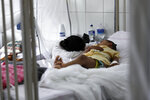In this photo taken on Aug. 20, 2019, a patient receives treatment for dengue and is taken care of by a relative inside a room at the University School Hospital in Tegucigalpa, Honduras. In a ward usually reserved for juvenile burn victims, children lay listlessly under mosquito nets next to worried parents. (AP Photo/Eduardo Verdugo)