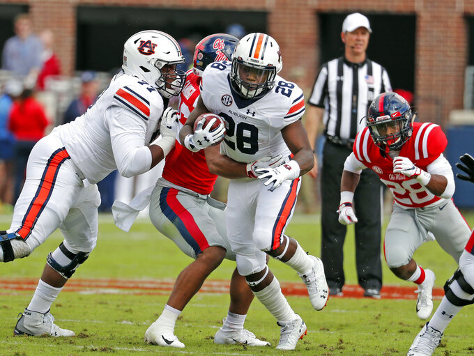 Auburn running back JaTarvious Whitlow (28) follows his blockers and runs for a short gain against Mississippi during the first half of an NCAA college football game on Saturday, Oct. 20, 2018, in Oxford, Miss. Auburn won 31-16. (AP Photo/Rogelio V. Solis)