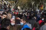 People enter the Rastro flea market in Madrid, Spain, Sunday, Nov. 22, 2020. Madrid's ancient and emblematic Rastro flea market reopened Sunday after a contentious eight-month closure because of the COVID-19 pandemic that has walloped the Spanish capital. (AP Photo/Paul White)