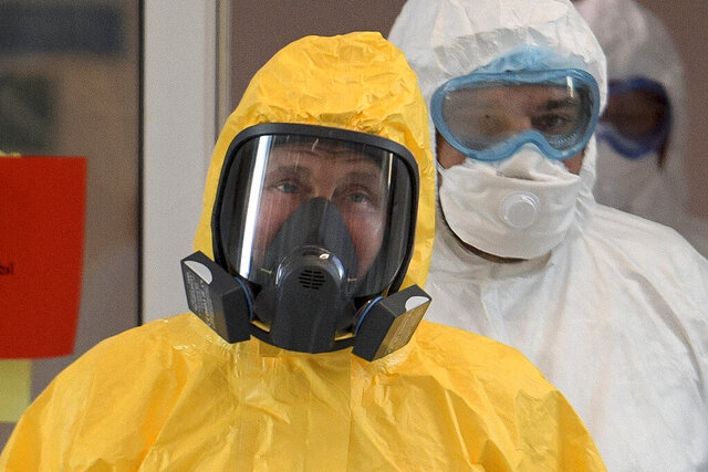 FILE - In this file photo taken on Tuesday, March 24, 2020, Russian President Vladimir Putin wearing a protective suit enters a hall during his visit to the hospital for coronavirus patients in Kommunarka, outside Moscow, Russia. Russian authorities declared a war on