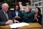 Democratic presidential candidate Sen. Elizabeth Warren, D-Mass., applauds after filing to have her name listed on the New Hampshire primary ballot, Wednesday, Nov. 13, 2019, in Concord, N.H. At left is New Hampshire Secretary of State Bill Gardner. (AP Photo/Charles Krupa)