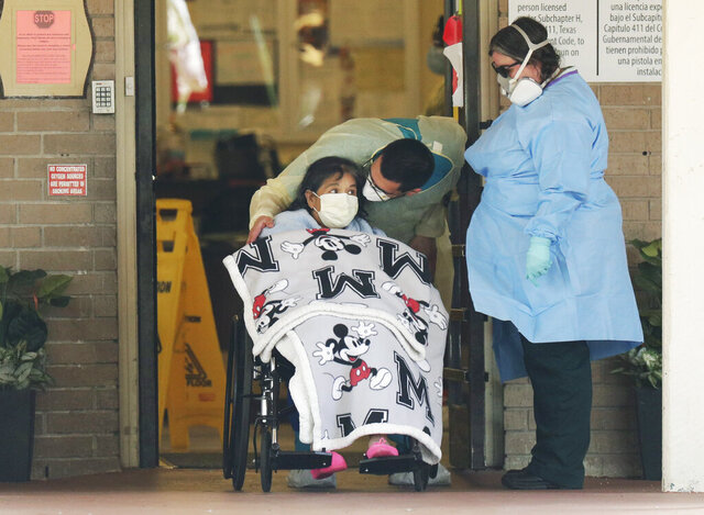 A resident is removed from the Southeast Nursing and Rehabilitation Center in San Antonio, Wednesday, April 8, 2020. More than 70 residents and staff have tested positive for COVID-19 at the facility and at least 10 residents have died due to the virus. (AP Photo/Eric Gay)