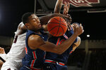 Auburn forward Anfernee McLemore (24), left, and guard Samir Doughty (10) fight with an unidentified Mississippi State player for a rebound during the first half of an NCAA college basketball game, Saturday, Jan. 4, 2020, in Starkville, Miss. (AP Photo/Rogelio V. Solis)