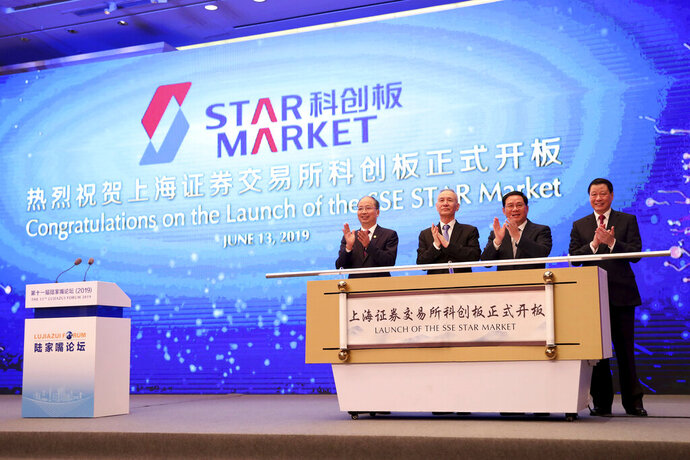 In this June 13, 2019, photo released by Xinhua News Agency, guests, from left, Yi Huiman, chairman of China Securities Regulatory Commission, Liu He, vice premier, Li Qiang, top party official of Shanghai, and Ying Yong, Shanghai's mayor, celebrate the launch of the SSE STAR Market, previously referred to as the Shanghai science and technology innovation board in Shanghai. Trading is expected to start Monday, July 22, 2019 on the Chinese stock market for high-tech companies that play a key role in official development plans that are straining relations with Washington. (Fang Zhe/Xinhua via AP)