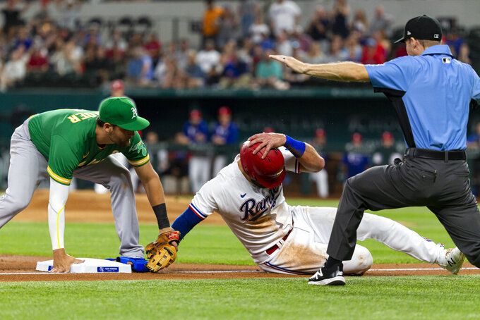 Texas Rangers' Joey Gallo, center, avoids the tag of Oakland Athletics third baseman Chad Pinder, left, to safely take third base during the first inning of a baseball game, Monday, June 21, 2021, in Arlington, Texas.(AP Photo/Sam Hodde)