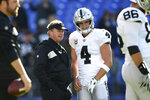 "FILE - In this Nov. 25, 2018, file photo, Oakland Raiders coach Jon Gruden, center left, speaks with quarterback Derek Carr before the team's NFL football game against the Baltimore Ravens in Baltimore. ""We have to win this year,"" Carr said. ""Nobody cares about what's after this. We have to win now. What's cool about this team is the expectation."" (AP Photo/Gail Burton, File)"