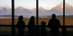 FILE - In this Aug. 28, 2016 file photo visitors watch the morning sun illuminate the Grand Tetons from within the Great Room at the Jackson Lake Lodge in Grand Teton National Park north of Jackson, Wyo. On Tuesday, March 24, 2020, the National Park Service announced that Yellowstone and Grand Teton National Parks would be closed until further notice, and no visitor access will be permitted to either park. (AP Photo/Brennan Linsley,File)
