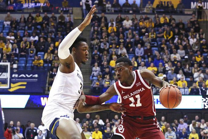 Oklahoma guard De'Vion Harmon (11) goes up court while defended by West Virginia forward Gabe Osabuohien (3) during the first half of an NCAA college basketball game Saturday, Feb. 29, 2020, in Morgantown, W.Va. (AP Photo/Kathleen Batten)
