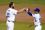 Los Angeles Dodgers starting pitcher Clayton Kershaw, left, high-fives Mookie Betts after the team's 3-0 win over the Milwaukee Brewers in Game 2 of a National League wild-card baseball series Thursday, Oct. 1, 2020, in Los Angeles. (AP Photo/Ashley Landis)
