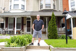 In this May 14, 2020 photo, Mark Weitkamp, who owns three recovery homes in York, Pa., poses in front of them. (Cameron Clark/York Daily Record via AP)