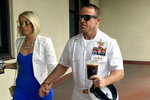 FILE - In this June 26, 2019 file photo, Navy Special Operations Chief Edward Gallagher, right, walks with his wife, Andrea Gallagher as they arrive to military court on Naval Base San Diego. The Navy has dismissed charges against an officer for allegedly not reporting war crimes by Gallagher, who was later acquitted of murder. A Navy official with knowledge of the decision not authorized to speak publicly confirmed charges against Lt. Jacob Portier were dropped Thursday, Aug. 1.  (AP Photo/Julie Watson, File)