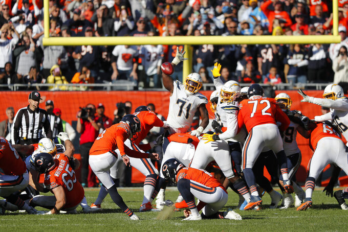 Chicago Bears kicker Eddy Pineiro, left, attempts a field goal on the final play of an NFL football game against the Los Angeles Chargers, Sunday, Oct. 27, 2019, in Chicago. Pineiro missed the field goal as the Chargers won 17-16. (AP Photo/Charles Rex Arbogast)