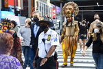 """Costumed cast members of Broadway's """"The Lion King,"""" L. Steven Taylor, as Mufasa, right, and and Tshidi Manye, as Rafiki, left, appear in Times Square to herald the return of Broadway theater in New York, Tuesday, Sept. 14, 2021. (Marc A. Hermann / Metropolitan Transportation Authority via AP)"""