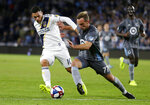 LA Galaxy forward Christian Pavon (10) and Minnesota United defender Chase Gasper (77) vie for the ball during the first half of an MLS soccer first-round playoff match, Sunday, Oct. 20, 2019, in St. Paul, Minn. (AP Photo/Andy Clayton-King)