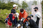 Staff members of tournament wearing face masks work on the 10th hole during the first round of the KLPGA Championship at the Lakewood Country Club in Yangju, South Korea, Thursday, May 14, 2020. (AP Photo/Lee Jin-man)