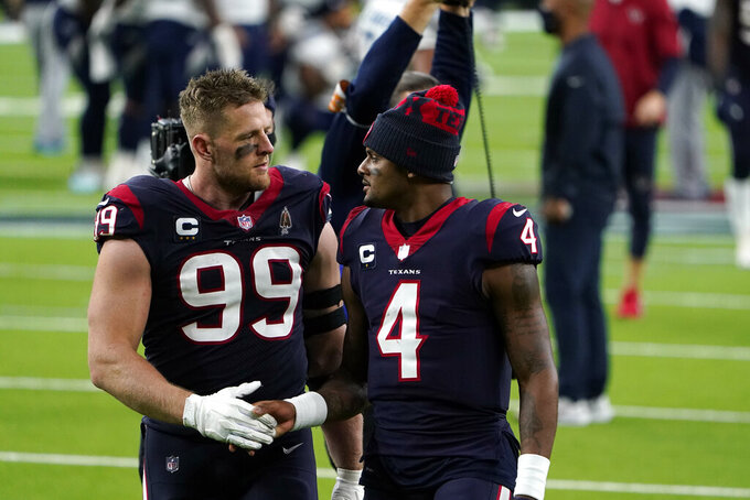 Houston Texans defensive end J.J. Watt (99) and quarterback Deshaun Watson (4) walk off the field after an NFL football game against the Tennessee Titans Sunday, Jan. 3, 2021, in Houston. The Titans won 41-38. (AP Photo/Eric Christian Smith)