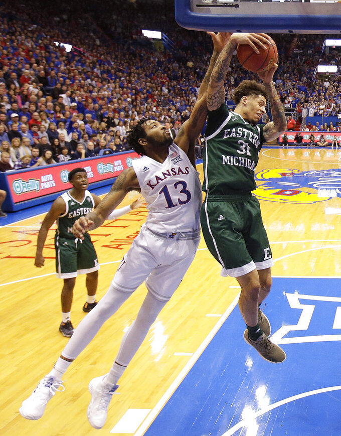 Kansas' K.J. Lawson (13) and Eastern Michigan's Ty Groce (31) battle for a rebound during the first half of an NCAA college basketball game Saturday, Dec. 29, 2018, in Lawrence, Kan. (AP Photo/Charlie Riedel)