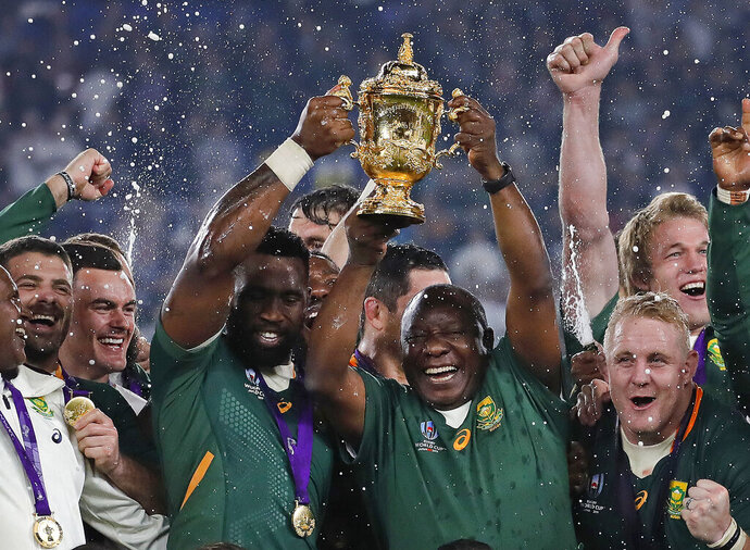 South African captain Siya Kolisi holds the Webb Ellis Cup aloft with South African President Cyril Ramaphosa after South Africa defeated England to win the Rugby World Cup final at International Yokohama Stadium in Yokohama, Japan, Saturday, Nov. 2, 2019. (AP Photo/Christophe Ena)