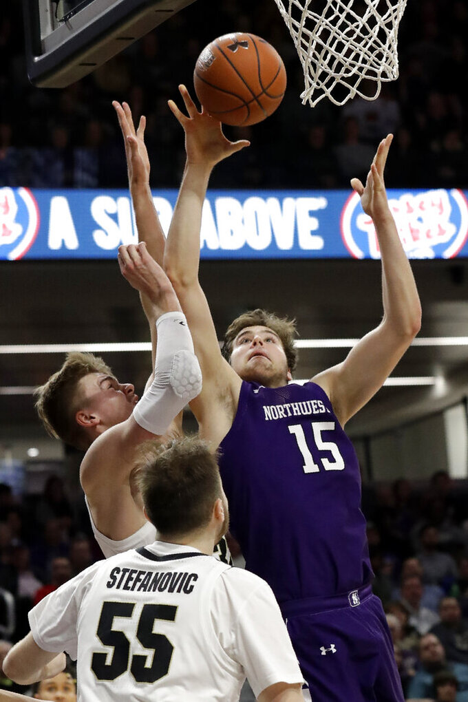 Northwestern center Ryan Young, right, shoots against Purdue center Matt Haarms during the second half of an NCAA college basketball game in Evanston, Ill., Saturday, Feb. 1, 2020. (AP Photo/Nam Y. Huh)