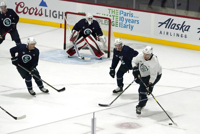 Seattle Kraken defenseman Jamie Oleksiak, right, looks to pass as he takes part in a practice session, Thursday, Sept. 9, 2021, during a media event for the grand opening of the Kraken's NHL hockey practice and community facility in Seattle. (AP Photo/Ted S. Warren)
