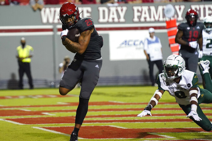 North Carolina State wide receiver Christopher Toudle (29) scores a touchdown while South Florida defensive back Christopher Townsel (8) misses the tackle during the second half of an NCAA college football game in Raleigh, N.C., Thursday, Sept. 2, 2021. (AP Photo/Gerry Broome)