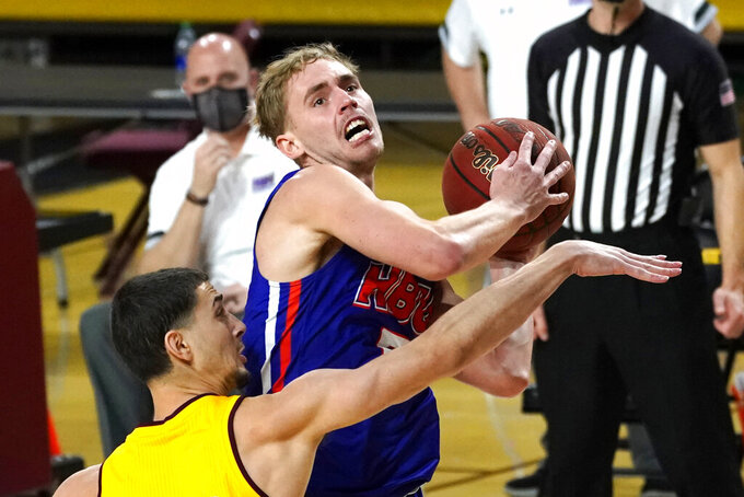 Houston Baptist guard Hunter Janacek, top, drives against Arizona State guard Kyle Feit during the second half of an NCAA college basketball game, Sunday, Nov. 29, 2020, in Tempe, Ariz. (AP Photo/Rick Scuteri)