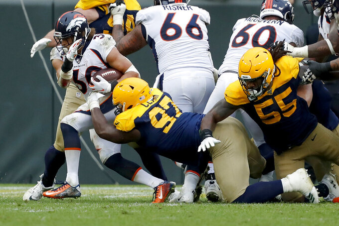Denver Broncos running back Phillip Lindsay, left, fights his way past Green Bay Packers nose tackle Kenny Clark (97) and outside linebacker Za'Darius Smith (55) for a touchdown during the second half of an NFL football game Sunday, Sept. 22, 2019, in Green Bay, Wis. (AP Photo/Matt Ludtke)