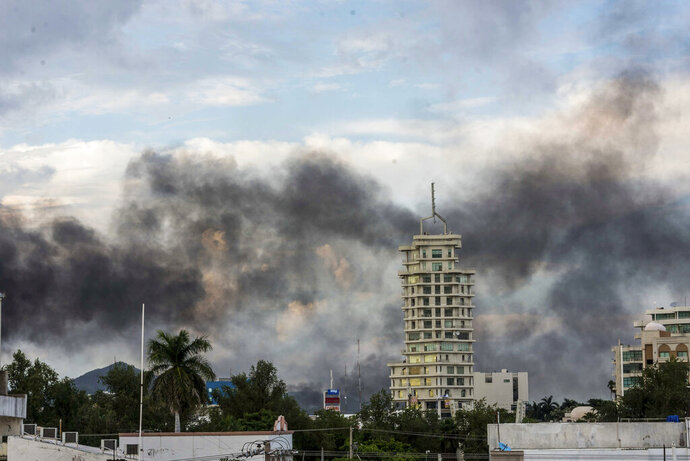 "Smoke from burning cars rises due in Culiacan, Mexico, Thursday, Oct. 17, 2019. An intense gunfight with heavy weapons and burning vehicles blocking roads raged in the capital of Mexico's Sinaloa state Thursday after security forces located one of Joaquín ""El Chapo"" Guzmán's sons who is wanted in the U.S. on drug trafficking charges. (AP Photo/Hector Parra)"